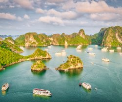 Scenic view from above over Halong Bay with cruising Tourboats and Tourist Passenger Ships in warm late afternoon light. Halong Bay is popular for the fantastic limestone karsts and isles. Halong Bay, Quang Ninh Province, Northern Vietnam, Vietnam, Southeast Asia