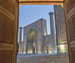 Samarkand, Uzbekistan - May 19, 2017: View over the madrassa in Registan Square, through wooden doors, in Samarkand, Uzbekistan.