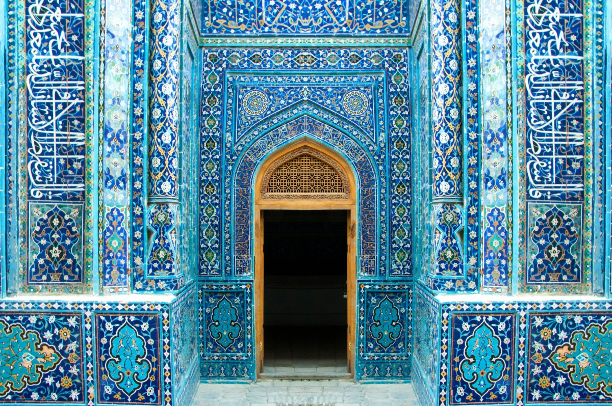 Symmetrical, richly decorated with blue ceramic islamic tiles, entrance and open door in Shah-I-Zinda